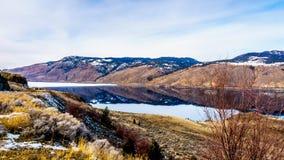 As corridas da estrada do transporte Canadá ao longo do lago Kamloops com as montanhas circunvizinhas que refletem no silêncio su Imagens de Stock Royalty Free
