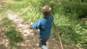 As corridas felizes do rapaz pequeno com haste riem e sorriem filme