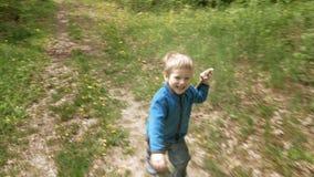 As corridas felizes do rapaz pequeno com haste riem e sorriem video estoque