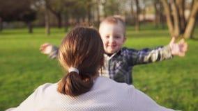 As corridas felizes do rapaz pequeno na mãe que o ` s abre o nd do armsa abraçam-na no parque da mola video estoque