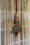 As cortinas de laço brancas na janela com feriado assinam dentro a madeira Fotografia de Stock