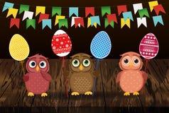 As corujas mantêm ovos decorados Páscoa em uma vara multicolored Vetor ilustração royalty free