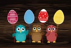 As corujas mantêm ovos decorados Páscoa em uma vara multicolored Vetor ilustração stock