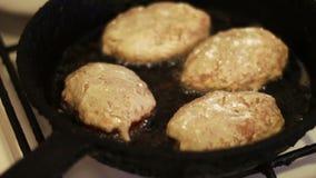 As costoletas para Hamburger são fritadas em uma frigideira na cozinha home video estoque