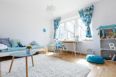As cosy as a child room can be. Very spacious and light child room with large window, filled with white and blue decorative elements stock photo