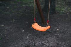 as crianças \ 's balançam em correntes no campo de jogos contra um fundo escuro as crianças \ 'laranja de s vacilam terra preta e fotografia de stock royalty free