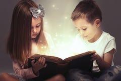 As crianças acoplam-se abriram um livro mágico Fotografia de Stock Royalty Free