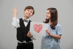 As crianças acoplam-se com coração pintado fotografia de stock royalty free