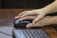 As crianças ajudam pessoas adultas a dominar o computador fotografia de stock royalty free