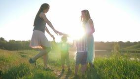 As crianças alegres conduzem a dança redonda que guarda as mãos no prado verde perto do lago na luz solar filme
