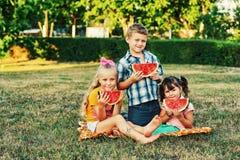 As crianças alegres estão felizes comer a melancia no ar fresco fotos de stock