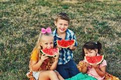 As crianças alegres estão felizes comer a melancia no ar fresco imagens de stock