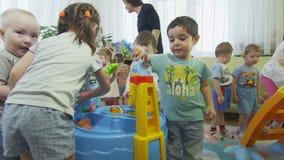 As crianças alegres jogam com os brinquedos plásticos na sala clara video estoque