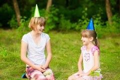 As crianças amigáveis em tampões festivos do cone, têm o divertimento junto como comemoram olhar do aniversário com expressões fe imagem de stock royalty free