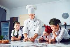 As crianças aprendem cozinhar na sala de aula na cozinha fotografia de stock