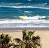As crianças aprendem surfar nas ondas do mar fotos de stock