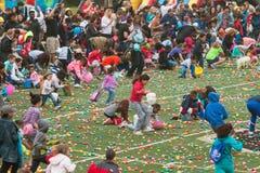 As crianças apressam-se no campo de futebol para a caça do ovo da páscoa da comunidade Fotos de Stock