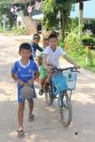 As crianças asiáticas estão montando bicicletas foto de stock