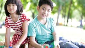 As crianças asiáticas felizes estão jogando o brinquedo em um parque filme
