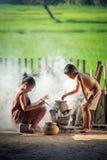 As crianças asiáticas menino e menina estão cozinhando na cozinha do Co imagem de stock