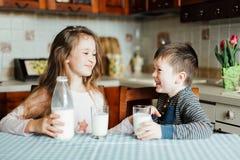 As crianças bebem o leite e têm o divertimento na cozinha na manhã A irmã e o irmão preparam o cacau Fotografia de Stock Royalty Free