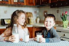 As crianças bebem o leite e têm o divertimento na cozinha na manhã A irmã e o irmão preparam o cacau Fotos de Stock Royalty Free