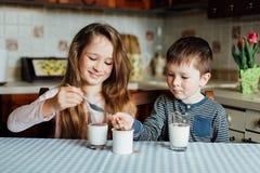 As crianças bebem o leite na cozinha na manhã A irmã e o irmão preparam o cacau Imagens de Stock