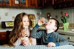 As crianças bebem o leite na cozinha na manhã A irmã e o irmão preparam o cacau Fotografia de Stock
