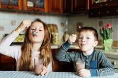 As crianças bebem o leite na cozinha na manhã A irmã e o irmão preparam o cacau Foto de Stock