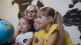 As crianças bonitos com professor sentam-se na tabela na sala de aula da geografia e estão estudando curiosamente o globo ou filme