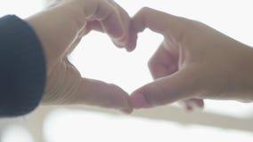 As crianças bonitos descrevem a forma do coração com seus dedos perto acima Coração dado forma pelas mãos da criança Conce video estoque