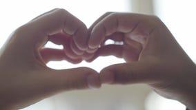 As crianças bonitos descrevem a forma do coração com seus dedos perto acima Coração dado forma pelas mãos da criança Conce filme