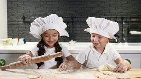As crianças bonitos em chapéus do cozinheiro chefe cozinham a casa das cookies e das tortas em privado Utensílio da cozinha no fu video estoque