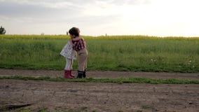 As crianças bonitos que abraçam-se, encontrando os amigos, correndo em torno da estrada do campo, movimento lento, menino e menin
