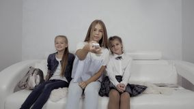 As crianças bonitos que olham a tevê no sofá em casa, as meninas saltam no sofá e tomam a tevê remota video estoque
