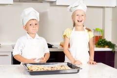 As crianças brancas no vestuário dos cozinheiros chefe fizeram a pizza Fotografia de Stock Royalty Free