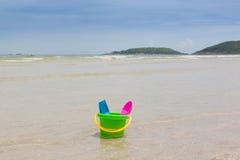 As crianças brincam, cubeta e colher coloridas na praia Foto de Stock Royalty Free