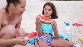 As crianças caçoam adolescentes em rir de descanso da praia e em comer o vídeo de movimento lento da melancia adolescente da meni video estoque