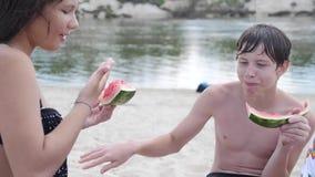 As crianças caçoam adolescentes em rir de descanso da praia e em comer o vídeo de movimento lento da melancia estilo de vida e me vídeos de arquivo