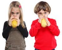 As crianças caçoam o formulário saudável bebendo do retrato comer do suco de laranja Foto de Stock Royalty Free
