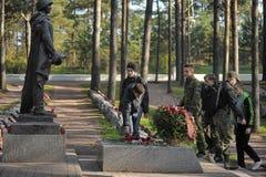 As crianças colocam flores no túmulo do soldado desconhecido imagem de stock royalty free