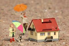 As crianças com guarda-chuvas, filhote de cachorro e casa modelam Fotos de Stock Royalty Free