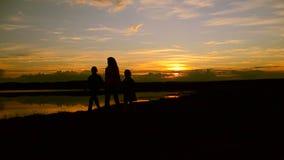 As crianças com mum andam na praia no por do sol filme