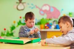 As crianças com necessidades especiais desenvolvem suas habilidades finas da mobilidade no centro de reabilitação da guarda imagem de stock