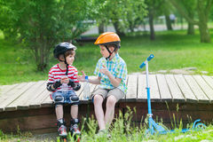 As crianças com rolos e 'trotinette' sentam-se em uma plataforma de madeira Fotografia de Stock