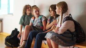 As crianças com sacolas sentam-se no corredor da escola, falando e rindo De volta ? escola vídeos de arquivo