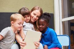 As crianças com uma tabuleta usam um app foto de stock