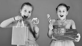 As crianças comem os caramelos doces coloridos grandes que abrem presentes Foto de Stock