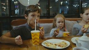 As crianças comem a pizza no café e comem batatas filme