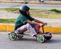 As crianças competem em torno do canto em carros de corridas de madeira caseiros Imagens de Stock Royalty Free